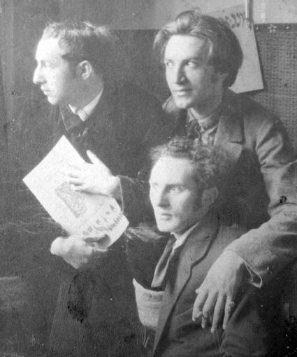 """Nazdjęciu odlewej: Marek Szwarc, Mojżesz (Mosze) Broderson (Broderzon, Brodersohn) iJankiel Adler prezentują drugi numer czasopisma """"Jung-Idysz"""", nr2-3. Łódź 1919,fotograf nieznany."""